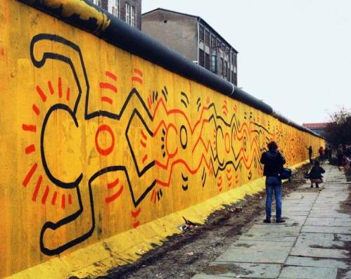 Mur de Berlin décoré et homme en noir